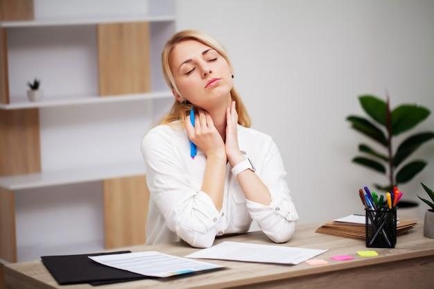 Müde junge geschäftsfrau am arbeitsplatz in ihrem büro erschöpft