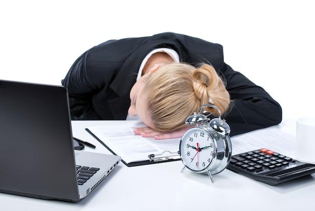 Müde junge geschäftsfrau, die nahe bei seinem laptop schläft.