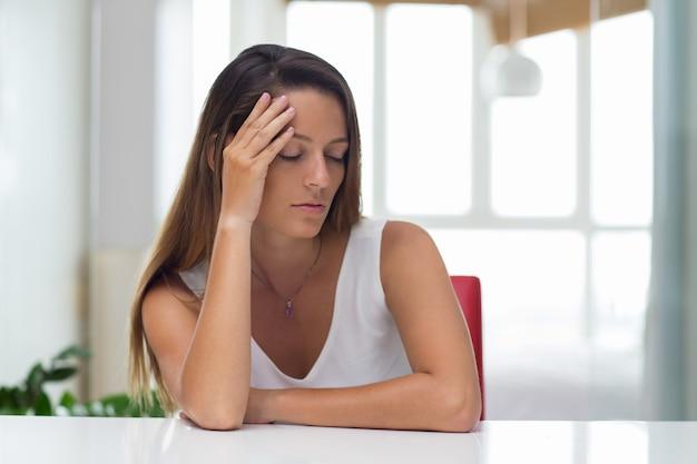 Müde junge geschäftsfrau mit schmerzen im kopf