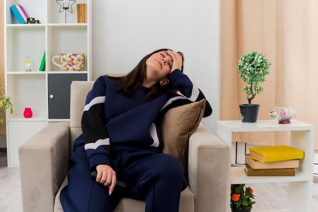 Müde junge hübsche kaukasische frau, die auf sessel in entworfenem wohnzimmer hält, das fernbedienung hält hand auf kopf mit geschlossenen augen setzt