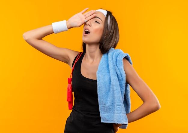 Müde junge hübsche sportliche mädchen tragen stirnband und armband mit handtuch und springseil auf ihren schultern setzen hand auf kopf auf orange raum