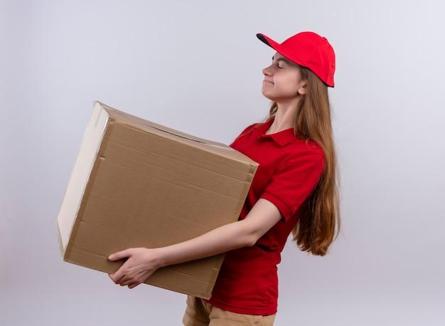 Müde junge lieferfrau in der roten uniform, die box hält, die in der profilansicht auf isolierter weißer wand steht