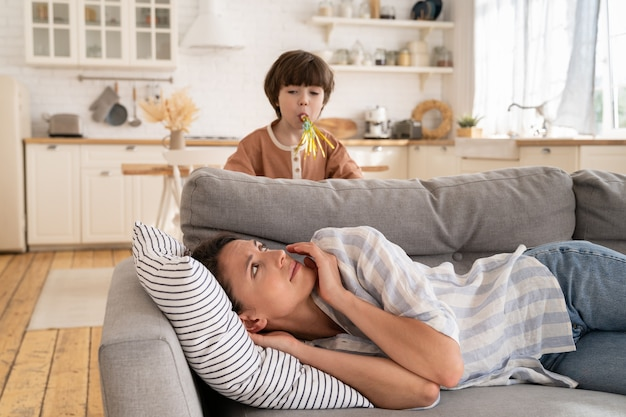 Müde junge mutter, die mit kleinem kind wach ist, macht geräusche erschöpfte mutter, die auf dem sofa liegt, versucht zu schlafen oder sich auszuruhen