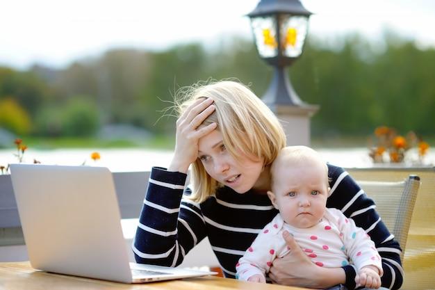 Müde junge mutter, die oh ihr laptop arbeitet und 6-monatige tochter hält