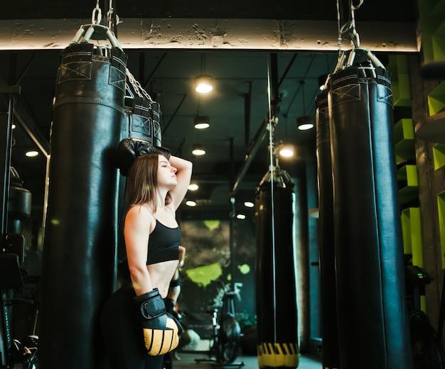Müde junge sportfrau, die nach schwerem boxtraining mit boxsack ruht