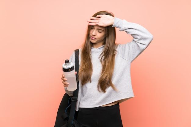 Müde junge sportfrau über lokalisiertem rosa mit einer flasche wasser