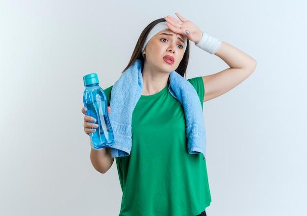 Müde junge sportliche frau, die stirnband und armbänder mit handtuch um hals hält wasserflasche hält hand auf stirn schaut seite