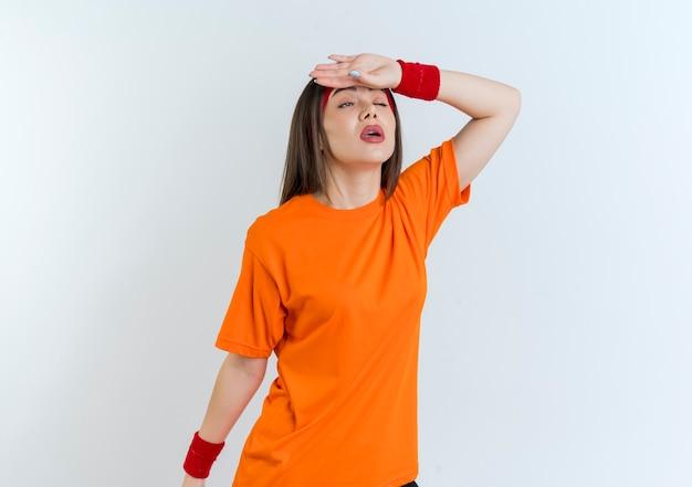 Müde junge sportliche frau, die stirnband und armbänder trägt, die gerade mit einem geschlossenen auge schauen und hand auf stirn isoliert halten