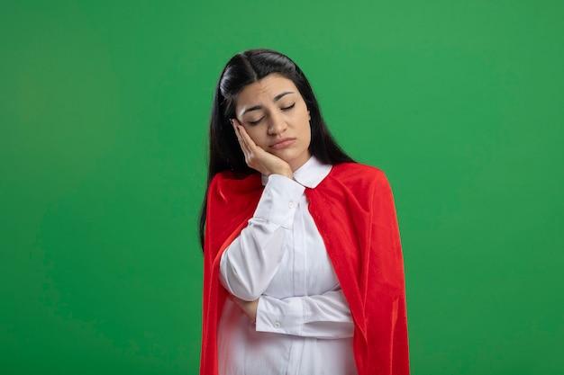 Müde junge superfrau, die ihr kinn mit der hand hält und auf füßen mit geschlossenen augen an grünen wänden nickerchen macht