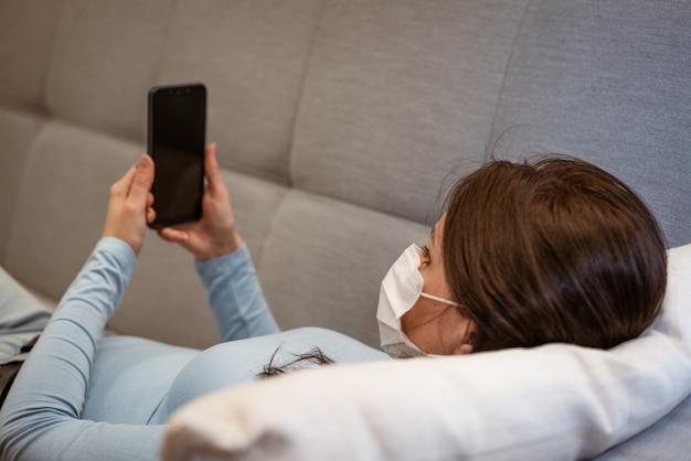 Müde kaukasierin in freizeitkleidung in einer schutzmaske auf der couch mit einem telefon
