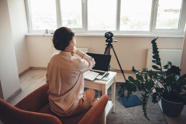 Müde kaukasische frau in der formellen kleidung, die online-treffen mit einer kamera und einem laptop beim sitzen am tisch im sessel hat