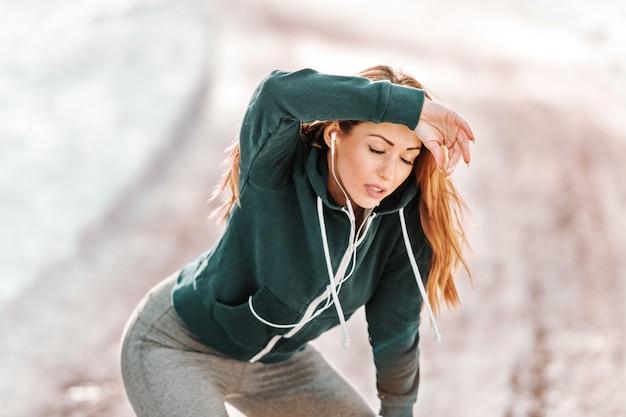 Müde kaukasische sportliche frau in der sportbekleidung, die vom laufen im freien im winter ruht.