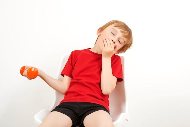 Müde kind nach dem training mit hanteln. junge ruht und sitzt auf dem stuhl. kinderfittnes. gesunde kindheit.