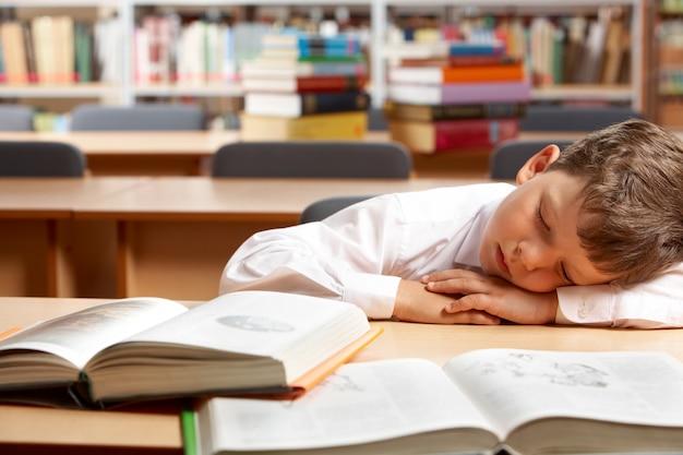 Müde kleiner junge in der bibliothek schlafen