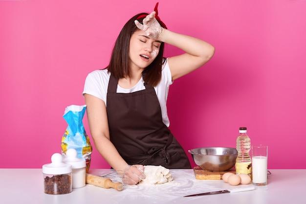Müde köchin steht mit geschlossenen augen am tisch in der küche, hält die hand auf der stirn, verbringt sich mit dem kneten von teig. junge frau predigt hausgemachtes gebäck am wochenende, gekleidet in t-shirt und schürze.