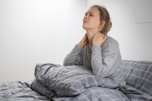 Müde kranke frau auf dem bett, die ihren hals berührt und unter schmerzen leidet