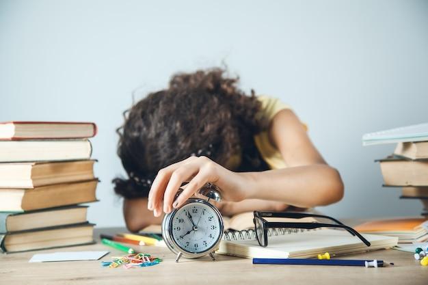 Müde lernende mädchenhand auf uhr auf tisch