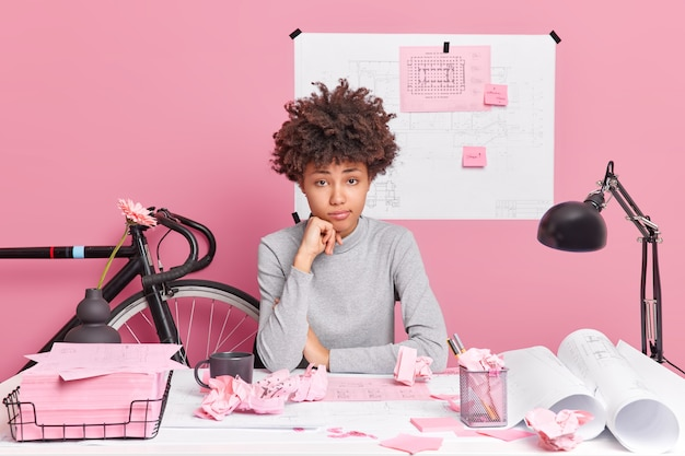 Müde lockige afroamerikanische studentin arbeitet an kursarbeitsprojekten versucht lösungen zu finden posen im coworking space zeichnet skizzen aufmerksam,