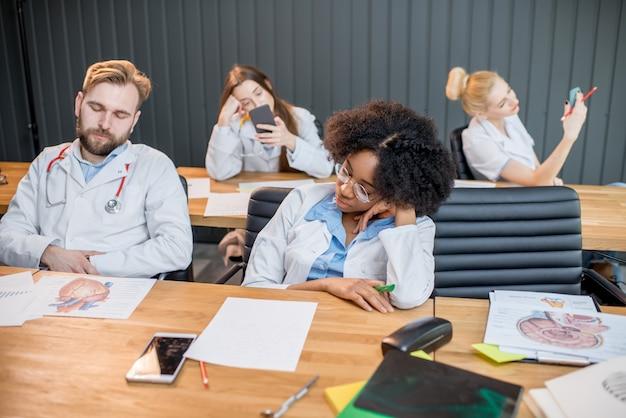 Müde medizinstudenten schlafen während des langweiligen unterrichts im klassenzimmer