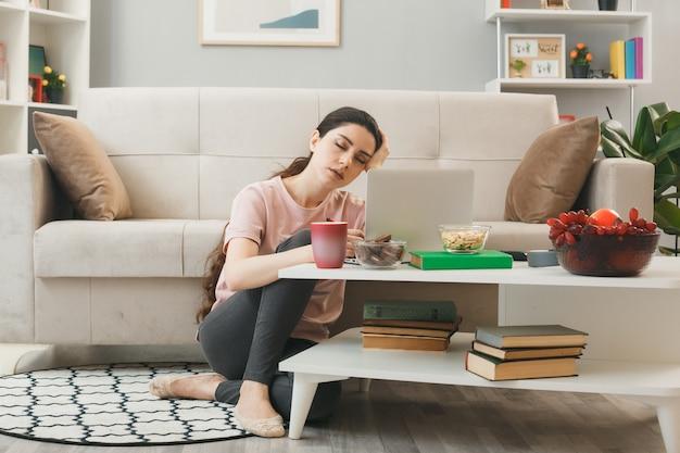Müde mit geschlossenen augen, die hand auf den kopf legen, junges mädchen, das auf dem boden hinter dem couchtisch im wohnzimmer sitzt?