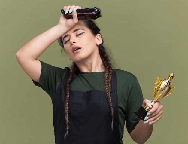 Müde mit geschlossenen augen junge weibliche friseurin in uniform, die haarschneidemaschinen mit siegerpokal hält hand auf stirn lokalisiert auf olivgrüner wand