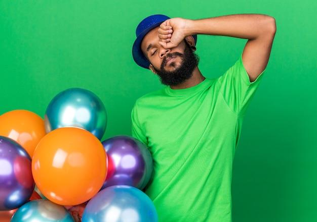 Müde mit geschlossenen augen junger afroamerikanischer kerl mit partyhut, der luftballons hält und das auge mit der hand abwischt