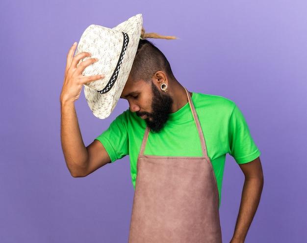 Müde mit geschlossenen augen junger gärtner afro-amerikaner, der gartenhut auf den kopf setzt