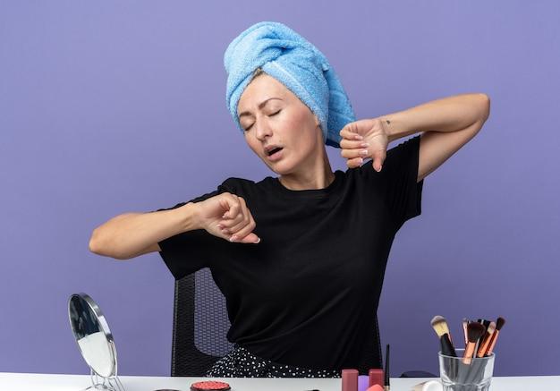 Müde mit geschlossenen augen sitzt das junge schöne mädchen am tisch mit make-up-tools und wischt sich die haare im handtuch ab und streckt die hände einzeln auf blauem hintergrund aus