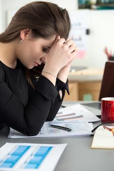 Müde mitarbeiterin am arbeitsplatz im büro berührt ihren kopf. schläfriger arbeiter am frühen morgen nach der späten nachtarbeit. überarbeitung, fehler, stress, beendigung oder depressionskonzept
