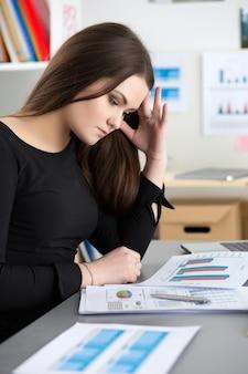 Müde mitarbeiterin am arbeitsplatz im büro berührt ihren kopf und versucht sich zu konzentrieren