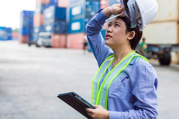 Müde müdigkeit der arbeiterin durch harte überlastung und heißes wetter im freien, das in der hafenfrachtschifffahrtsindustrie schwitzt.