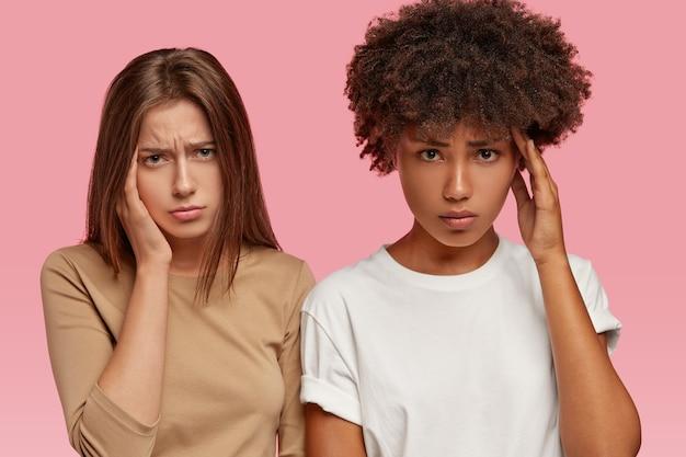 Müde multiethnische freunde haben kopfschmerzen nach lauten diskussionen beim treffen, schauen missmutig von der stirn, halten die hand an der schläfe, haben mürrische gesichtsausdrücke, isoliert über der rosa wand