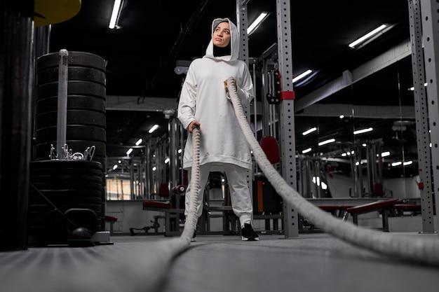 Müde muslimische frauen machen eine pause während cross-fit-übungen mit einem seil. junge schöne frau im sportlichen hijab steht mit ruhe. im fitnessstudio
