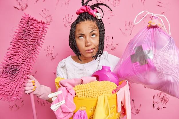 Müde, nachdenkliche hausfrau posiert mit müllsack und mopp steht schmutzig nach hausarbeit reinigt haus verwendet reinigungsmittel trägt gummischutzhandschuhe hat dreadlocks isoliert auf rosa wand