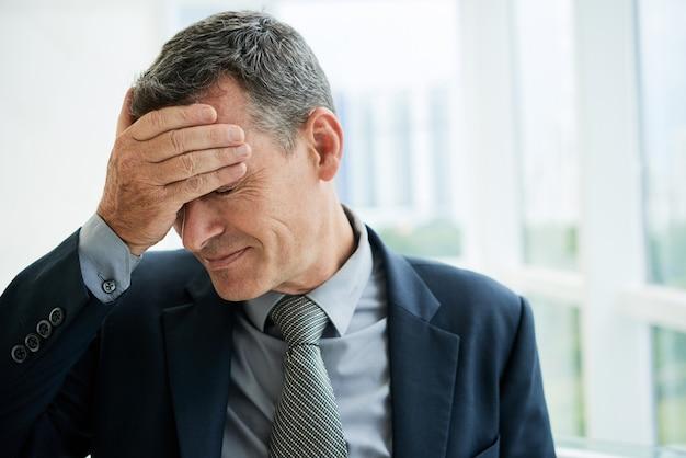 Müde oder enttäuschte reife männliche führungskraft mit krawatte, die die stirn berührt, während sie kopfschmerzen oder erhöhte temperatur verspürt