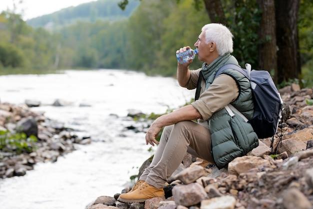 Müde reifen backpacker trinkwasser aus plastikflasche beim sitzen am flussufer in natürlicher umgebung