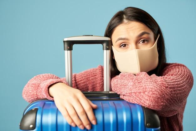 Müde reisende in schutzmaske in der nähe von gepäck