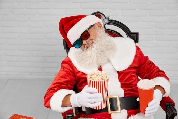 Müde santa claus, die im stuhl mit popcorn und kolabaum schläft