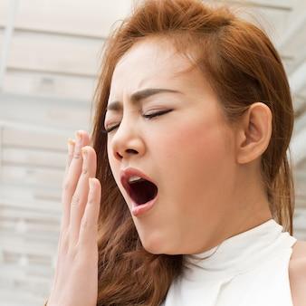 Müde, schläfrige frau gähnen mit müdigkeit oder schlaflosigkeit