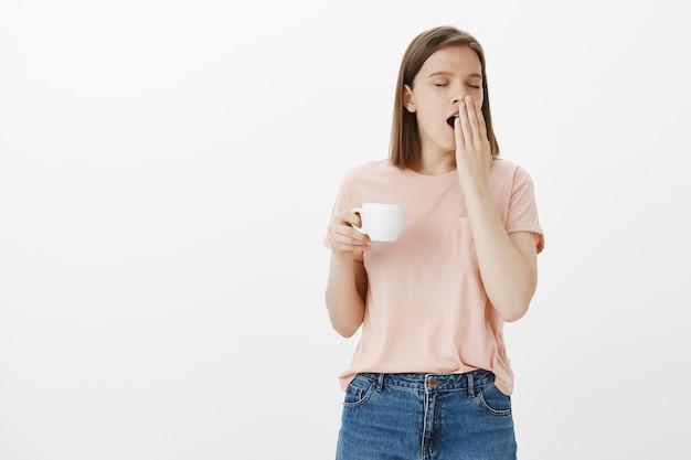 Müde schläfrige frau mit tasse kaffee gähnen