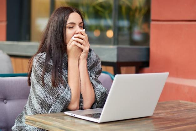 Müde schläfrige unternehmerin gähnt vor modernen laptop-computer, taille für feedback, arbeitet am geschäftsbericht