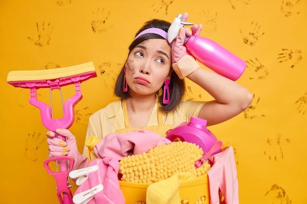 Müde schmutzige hausfrau wischt schweiß von der stirn, die beschäftigt ist, das haus zum funkeln zu bringen, hält waschmittelmop zum waschen des bodens verwendet reinigungsmittel verbringt viel zeit damit, stände in der nähe des wäschekorbs aufzuräumen