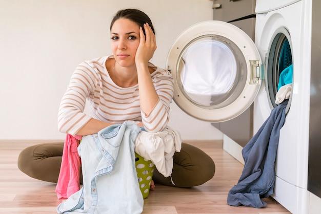 Müde schöne frau in der waschküche