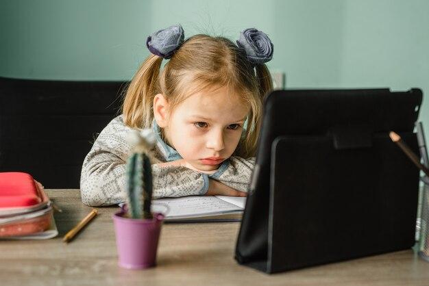 Müde schülerin, die sich auf ihre arme stützt, während sie zu hause online-unterricht hat