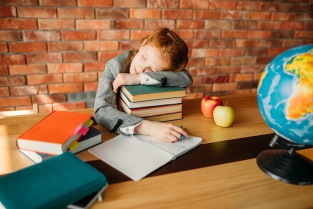 Müde schülerin schläft auf dem stapel lehrbücher am tisch mit geöffnetem notizbuch.