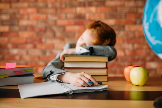Müde schülerin schläft auf stapel lehrbücher