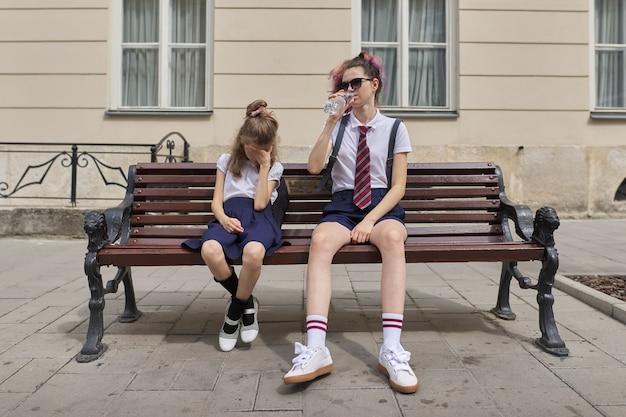 Müde schulkinder sitzen auf bank. zwei mädchen schwestern teenager und grundschüler