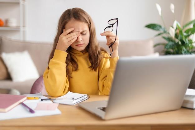 Müde schulmädchen reiben sich die augen, halten brillen, erschöpft vom lernen zu hause und hausaufgaben machen