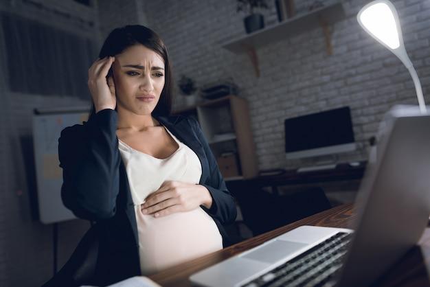 Müde schwangere frau, die kopfschmerzen im büro hat
