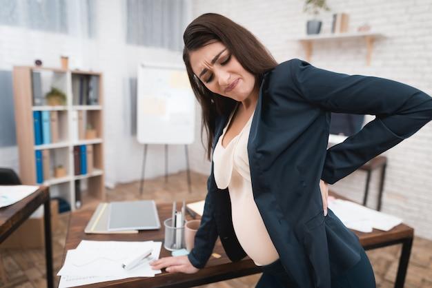 Müde schwangere frau, die rückenschmerzen bei der arbeit hat